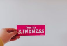 Woman holding fuscia sign Practice Kindness