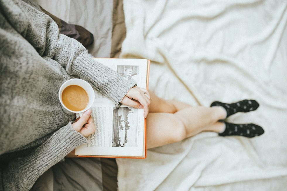 woman holding book and a cup of coffee